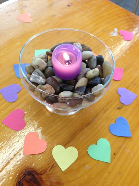 glass chalice filled with rocks and surrounded by multi-colored paper hearts